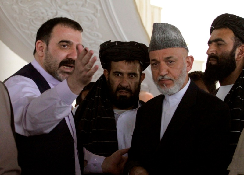 Afghan President Hamid Karzai, second from right, is met by his half brother Ahmad Wali Karzai, left, in Argandab district of Kandahar province, south of Kabul, Afghanistan, Saturday, Oct. 9, 2010. Karzai flew to southern Afghanistan to meet with more than 200 tribal elders and seek their support for his government's effort to extend its influence beyond Kabul. (AP Photo/Allauddin Khan)